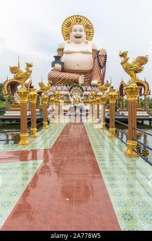 Ko Samui Island, Thailand - March 18, 2019: Wat Laem Suwannaram Chinese Buddhist Temple. Long shot on Giant statue of Budai with smaller statue of Lor - Stock Photo