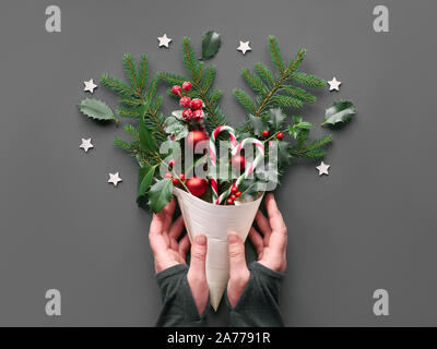 Creative Christmas flat lay in green and red on grey paper. Hand holding veneer cone with natural Xmas decorations: fir and holly twigs, baubles, cand - Stock Photo