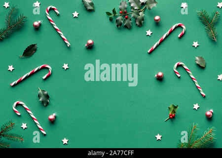 Trendy geometric Christmas flat lay on green paper background with candy canes, holly and fir twigs, wooden stars and glass trinkets with copy-space - Stock Photo