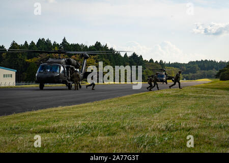 U.S. Marines exit a U.S. Army Sikorsky UH-60 Black Hawk during Black Hawk integration training as part of exercise Fuji Viper 20-1 on Camp Fuji, Japan, Oct. 28, 2019. Fuji Viper is a regularly scheduled training evolution for infantry units assigned to 3rd Marine Division as part of the unit deployment program. The training allows units to maintain their lethality and proficiency in infantry and combined arms tactics. (U.S. Marine Corps photo by Cpl. Timothy Hernandez) - Stock Photo