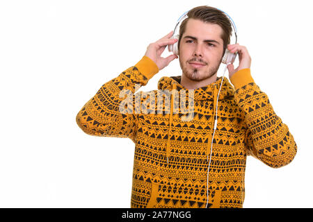 Portrait of young handsome bearded man with headphones - Stock Photo