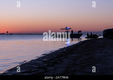 Silhouette of boat of Florida fish and wildlife officers at Dunedin Causeway in Dunedin, Florida, USA. Beautiful scenic seascape at sunset. Dunedin is - Stock Photo