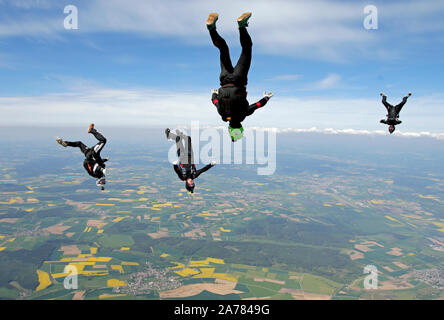 Four skydivers are trying to fly togehter in a formation with a speed of over 120mph. However they are tracking around each other and having fun! - Stock Photo