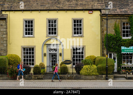 2 women walk past exterior of attractive antiques shop (Georgian building) & Dalesman Café Tearoom - village of Gargrave, North Yorkshire, England, UK - Stock Photo