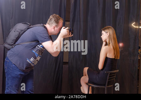 Photographer shooting using digital camera a model in the studio. - Stock Photo