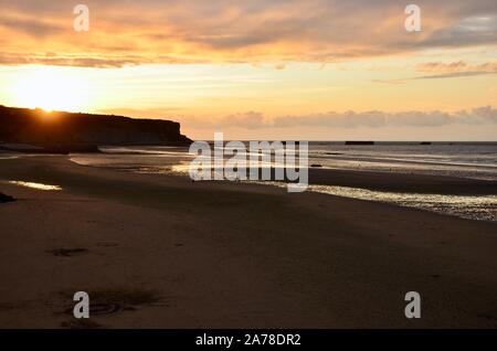 Sunset on the beach of Arromanches-les-Bains in Normandy, France, one of the allied landing places on D-Day, former loading ramps on horizon, summer - Stock Photo