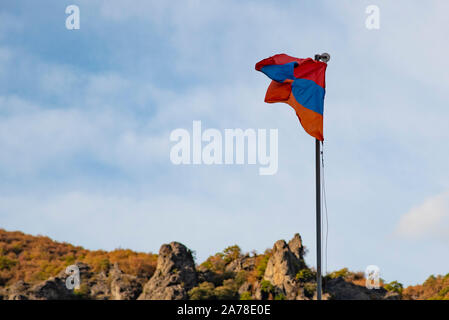 Armenian flag on a background of cloudy sky and autumn mountains. - Stock Photo