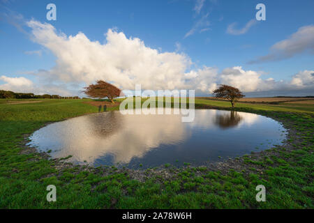 Dew pond with dramatic clouds on Ditchling Beacon, Ditchling, South Downs National Park, East Sussex, England, United Kingdom, Europe - Stock Photo
