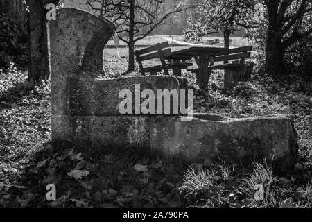 A black and white photograph of an old well in Germany. - Stock Photo