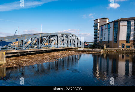 Leith, Edinburgh, Scotland, United Kingdom, 31st October 2019. UK Weather: Sunshine reflects buildings in the Water of Leith. Flotsam and jetsam debris due to high rainfall this year fills the basin by the old Victoria swing bridge, which an unsightly mess for local residents - Stock Photo