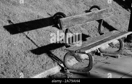 Old park bench with a shadow - Stock Photo