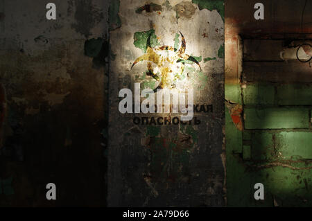 Biohazard warning on old damaged wall. Destroyed and forgotten building after disaster. Biology danger symbol alert. - Stock Photo