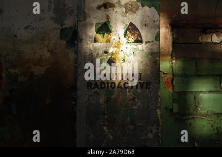 Radioactive warning on old damaged wall. Destroyed and forgotten building after nuclear disaster. Radiation symbol alert. - Stock Photo