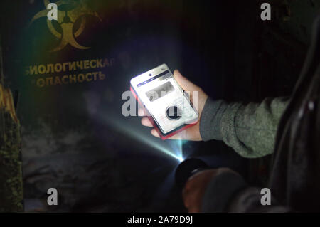 A man with a biohazard meter and a flashlight before a warning about danger. Virus and biology warning symbol on destroyed wall. 3D rendering illustra - Stock Photo