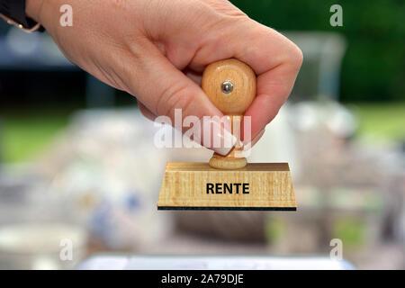 Hand mit Stempel, Frauenhand, Aufschrift: Rente - Stock Photo