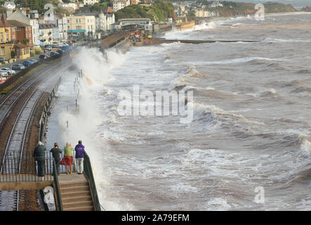 Rough sea at Dawlish as a diesel multiple unit leaves the station, heading for Paignton. - Stock Photo