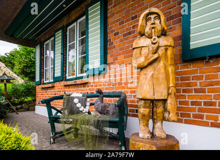 woodcarving of a baltic fisherman at a garden in the fishing village Gothmund at River Trave near Lübeck, Schleswig-Holstein, Germany - Stock Photo