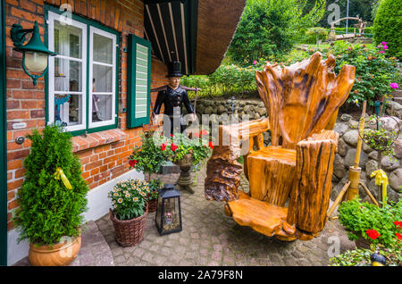 armchair carved from a tree trunk at the fishing village Gothmund at River Trave near Lübeck, Schleswig-Holstein, Germany - Stock Photo