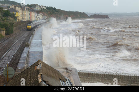 Rough sea at Dawlish as a Cross Country high speed train passes two joggers on the sea wall. - Stock Photo