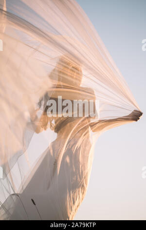 Beautiful silhouette of a woman bride in a long white dress and veil in the afternoon at sunset against the blue sky - Stock Photo