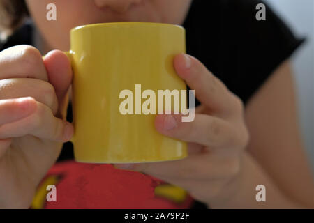 girl drinking hot tea from a yellow mug to get warm. - Stock Photo
