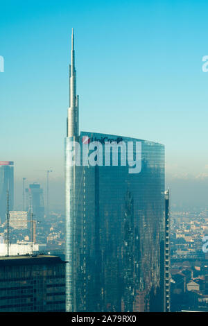 Milan Italy: Milan skyline, aerial view of the Unicredit bank headquarters skyscraper. City covered by smog. - Stock Photo