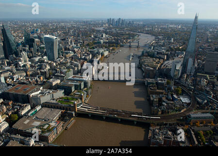 An aerial view looking east down the River Thames with the Shard and London Bridge.