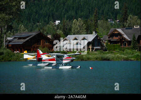 Seaplanes float on Green Lake in Whistler, British Columbia, Canada. - Stock Photo