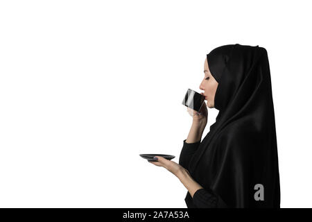 Beautiful Muslim woman in black hijab with pleasure drinks coffee or tea on white background, isolate. Concept, template or mockup for advertisements, - Stock Photo