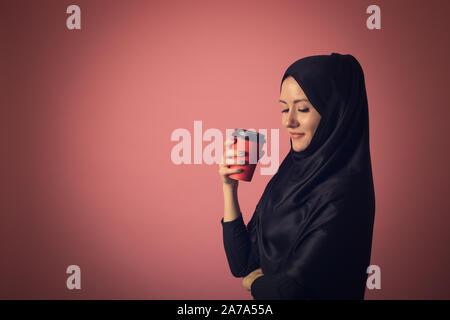 A beautiful Muslim woman with a mysterious look is drinking coffee from a red cup on a pink background in the studio. Concept for street advertising o - Stock Photo