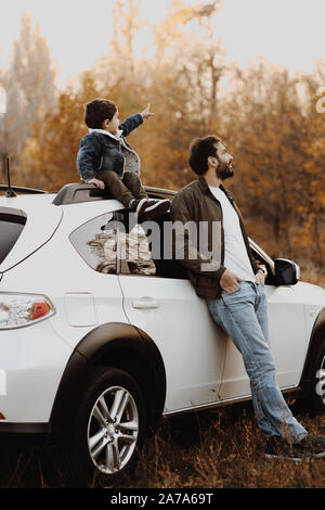 Happy father stanting near the car with his little son sitting on car and pointing at sky.