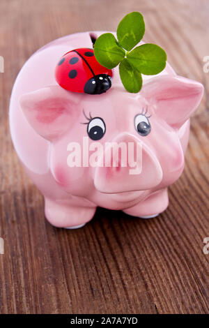 Pink lucky pig with lucky clover on a wooden backgurd - Stock Photo