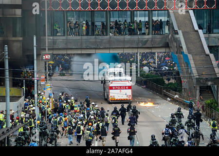 Hong Kong riot police charge towards pro-democracy protestors during violence after pro-democracy march in Hong Kong - Stock Photo