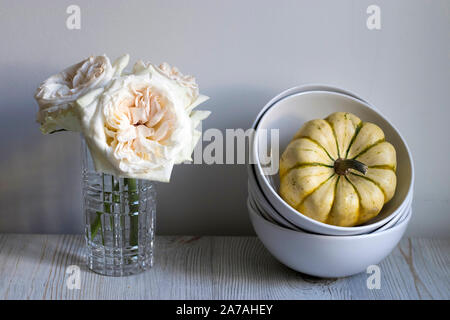 A bouquet of white roses in a glass vase and pumpkins in a bowl on a white table as a decoration of the kitchen interior - Stock Photo