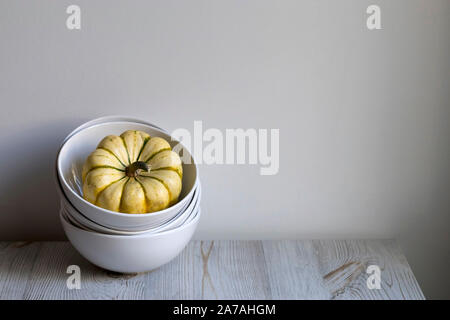 pumpkins in a bowl on a white table as a decoration of the kitchen interior - Stock Photo