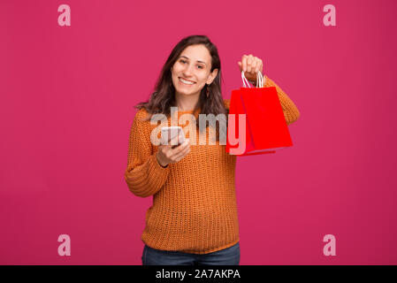 Image of young happy woman holding smartphone and shopping bags, online shopping - Stock Photo