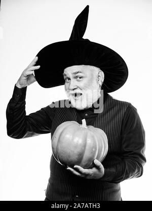 Fantastically good fun. Stargazer in holiday costume. Traditional food. bearded man ready for halloween party. evil wizard hold orange pumpkin. happy - Stock Photo