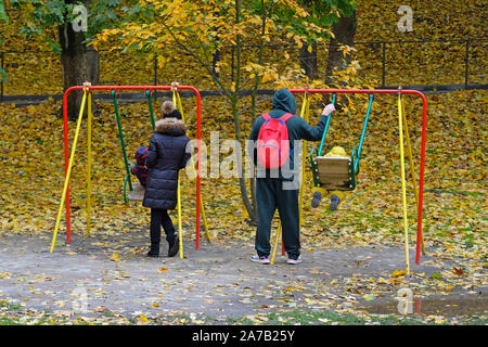 Children's swing in the autumn park. A girl and a man with a red backpack ride children on a swing. Rest in the autumn park with family. - Stock Photo
