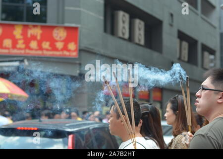 Asian people praying in Chinese temple with incense joss sticks during Lunar Chinese New Year festival - Stock Photo
