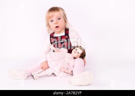 Little blonde toddler girl with big Blue Eyes in red dress play with old doll. Sitting on the floor, white background. Portrait, close-up isolated - Stock Photo