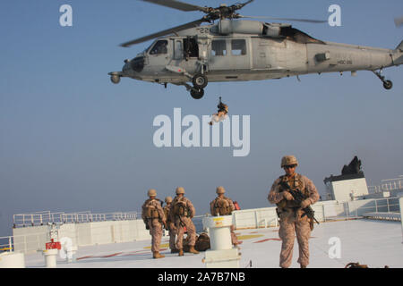 STRAIGHT OF HORMUZ (Oct 24, 2019) Marines assigned to Fleet Anti-Terrorism Security Team, Central Command (FASTCENT) prepare to be extracted by a Navy MH-60S Seahawk, attached to Helicopter Sea Combat Squadron 26 (HSC-26) from the Arc Liberty, a Military Sealift Command time chartered vessel, after providing security during a Strait of Hormuz transit. FASTCENT Marines work with U.S. partners and allies to protect personnel and property while simultaneously ensuring freedom of navigation in international waterways. Task Force 51 and 5th Marine Expeditionary Brigade is entrusted with rapidly agg - Stock Photo