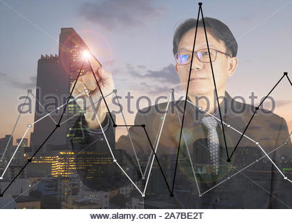 business man point graph in the city scape - Stock Photo
