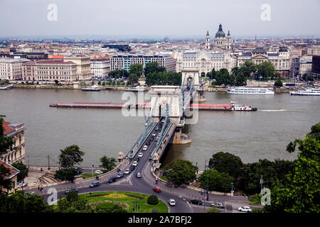 A barge on the Danube River passes under the Chain Bridge (Szechenyi Lanchid) in Budapest. - Stock Photo