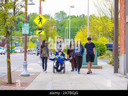 Disabled biracial boy in wheelchair walking along city street with father, siblings and caregiver, holding hands - Stock Photo
