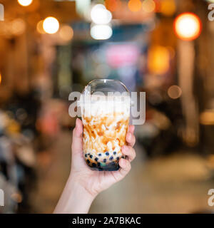 Young woman is holding, drinking brown sugar flavored tapioca pearl bubble milk tea with glass straw in night market of Taiwan, close up, bokeh - Stock Photo