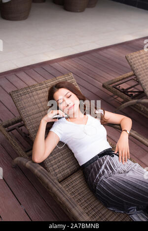 summer holidays, woman relaxing while listening to music and siiting in deckchair - Stock Photo
