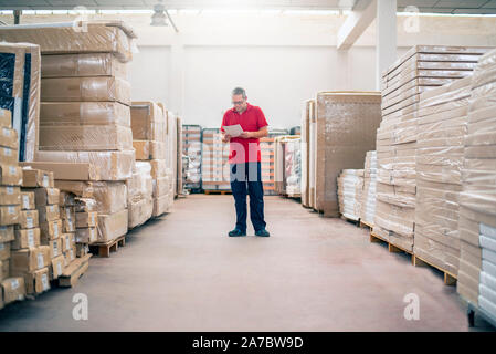 Warehouse employee checking the stock of stored products - Stock Photo
