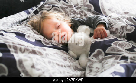 Adorable little Toddler girl with blonde hair slipping in big parents bed Day time nap Close-up - Stock Photo