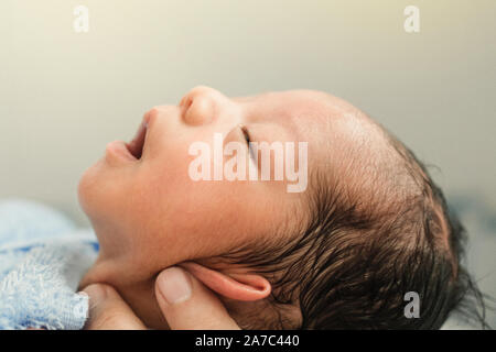 asian newborn baby boy is feeling relaxed and sleepy after taking bath at the first time of life. mother or father closing ears of newborn baby to bat - Stock Photo