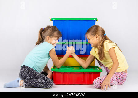 Two girls fight on hands, putting elbows on a box with toys - Stock Photo